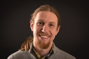 Head and shoulders image of Stephen Ullstrom, indexer, smiling at viewer. He is a young man with long reddish-brown hair in a ponytail.